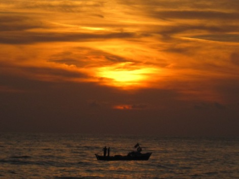 Solnedgång och fiskebåt vid Kleopatrastranden i Alanya